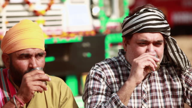Two truck drivers drinking tea at a tea stall, Ballabgarh, Haryana, India