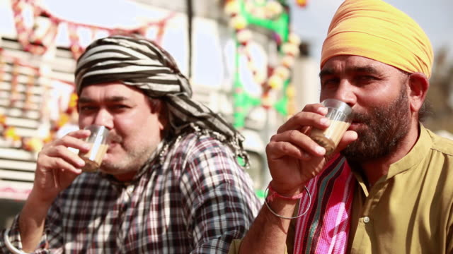 two truck drivers drinking tea at a tea stall, ballabgarh, haryana, india - heavy goods vehicle stock videos & royalty-free footage