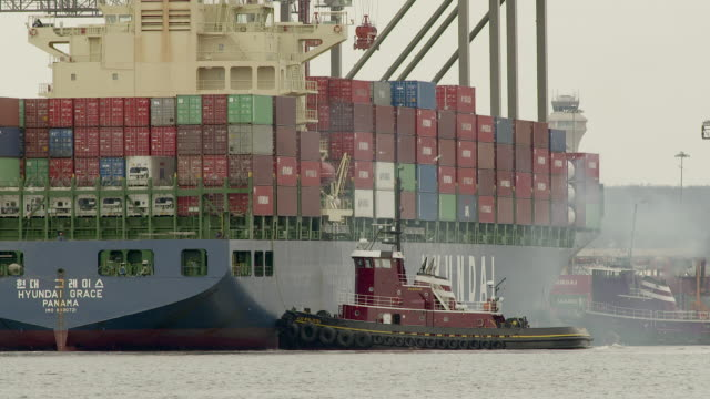 """two tug boats turn a large container ship at the port of newark on newark bay.   the ships name is """"hyundai grace"""" - grace bay stock videos and b-roll footage"""