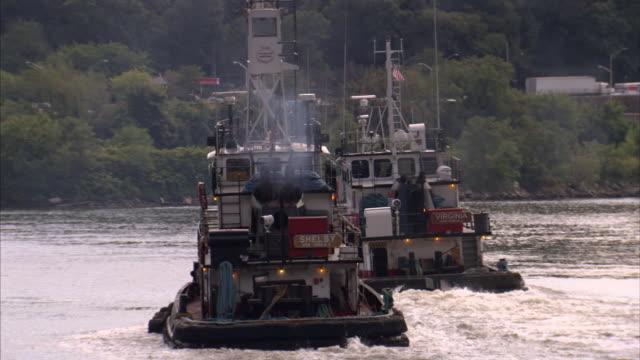 Two tugboats chug across a river.