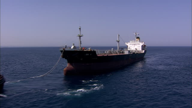 two tugboats tow an oil tanker on the mediterranean sea. - rimorchiare video stock e b–roll