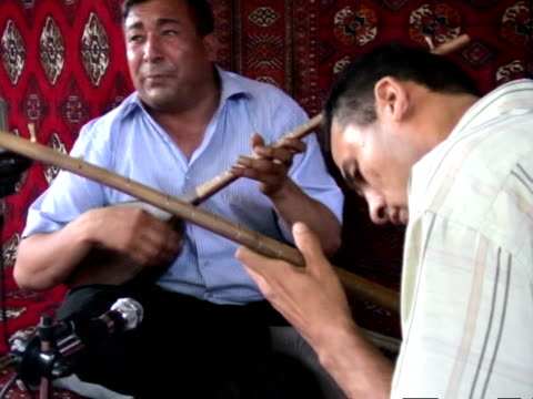 two turkmen musicians performing dutar and singing during bakhshi musical contest, ashghabad, turkmenistan, audio - solo uomini di età media video stock e b–roll