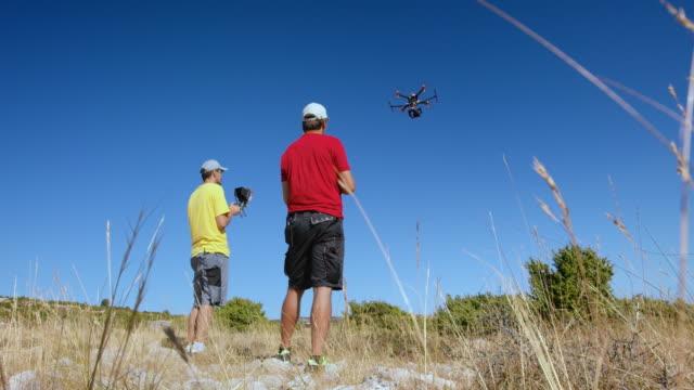 Zwei UAV Piloten steuern Drohne Start auf sonnigen Hügel