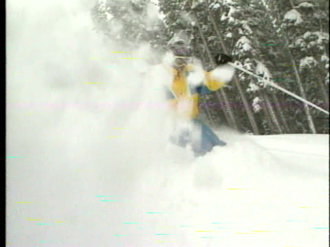 vídeos de stock e filmes b-roll de two unidentifiable male skiers wearing goggles skiing down hill w/ fluffy white snow passing snow covered trees bg winter christmas vacation get away... - roupa de esqui