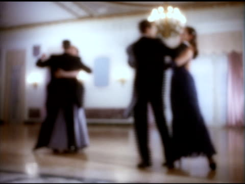 two unidentifiable partners fg bg elegantly dressed in ballroom hall dancing females dipping males males swinging out repeated moves reversed roles - ballroom stock videos & royalty-free footage