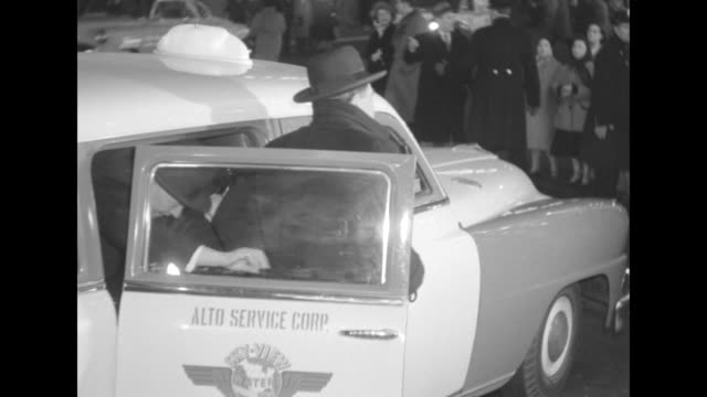 Two unidentified men get out of an Alto Service Corp cab at the premiere of The Eddie Cantor Story
