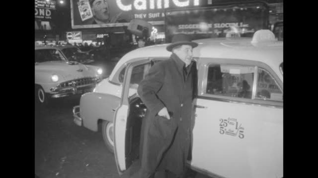 Two unidentified men in hats get out of cab at NYC premiere of The Eddie Cantor Story / unidentified couple waves