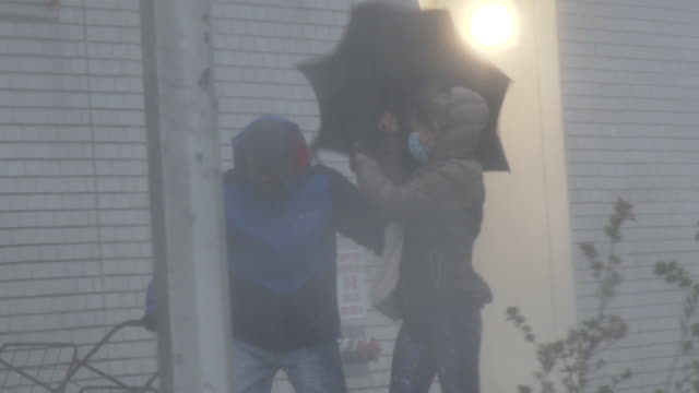 two unidentified people one wearing a surgical face mask and struggling with an umbrella attempt to walk in high winds and torrential rain on... - scott mcpartland stock videos & royalty-free footage