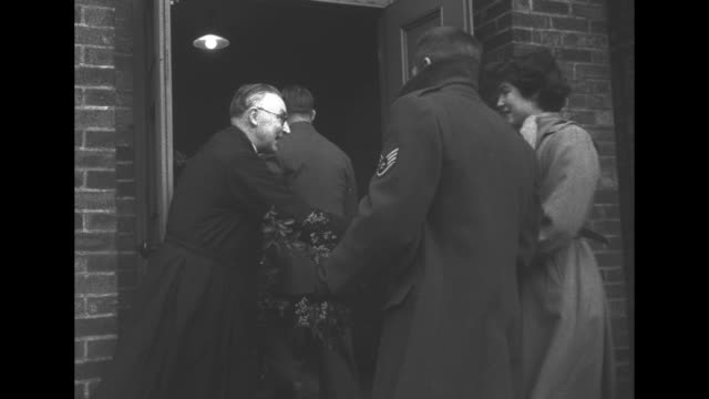 two uniformed men, women, and a little boy walk to st. michael's church in burtonwood carrying branches of greenery; they are welcomed at the door by... - キリスト降誕点の映像素材/bロール