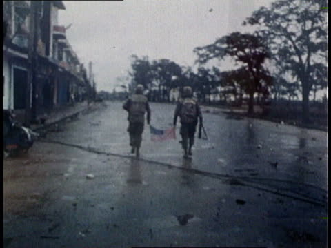 two united states soldiers walking down deserted street in vietnamese city holding small american flag between them / south vietnamese flag being... - guerra del vietnam video stock e b–roll