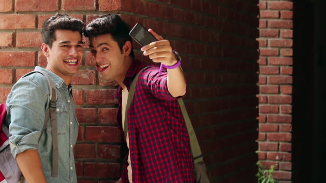 Two university students taking selfie with a mobile phone, Noida, Uttar Pradesh, India