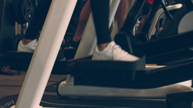 two unrecognizable athletes working out on elliptical machines at the gym - cardiovascular exercise stock videos & royalty-free footage