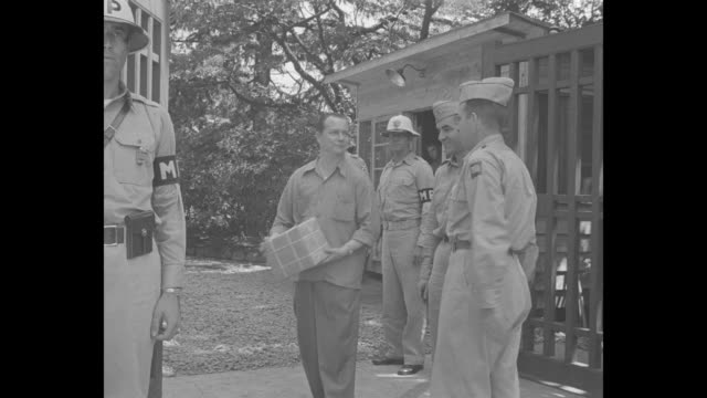 two us army officers, members of tokyo war crimes tribunal, walk up to entrance of hattori house compound, one carrying verdicts in briefcase, us mps... - mp stock-videos und b-roll-filmmaterial