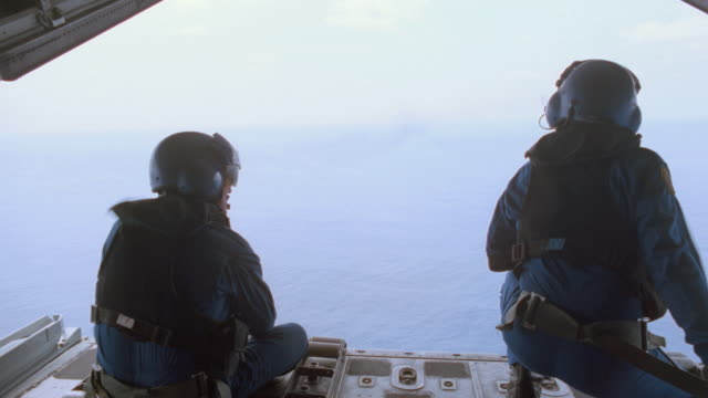 two u.s. coast guard crewmen kneel at the opening of a cargo plane as it flies over the ocean. - 1996 stock videos & royalty-free footage