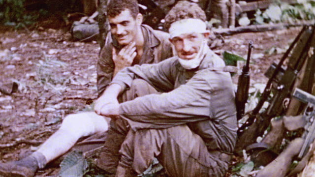 vidéos et rushes de two us marines one with bandages on his forehead and chin sitting on the ground at base / talasea new britain papua new guinea - blessure physique