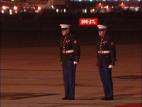 two us marines stand to attention, leaning into the wind and then marching off as helicopter containing president george w. bush departs at heathrow... - wind点の映像素材/bロール