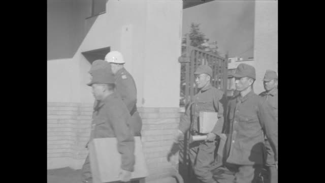two us mps open inner gates of sugamo prison, mps lead japanese prisoners out of building, they walk towards open gate / prisoners walk through open... - pacific war点の映像素材/bロール