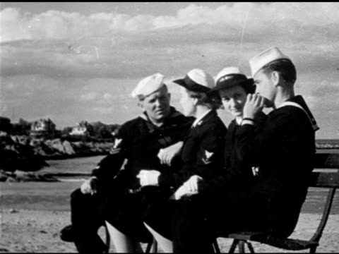 Two US Navy WAVES sitting w/ two US sailors at beach one young male adult sailor smoking cigarette while talking