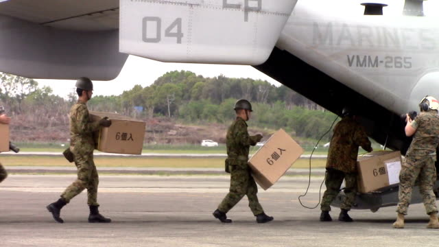 two u.s. osprey aircraft are loaded with disaster relief supplies at ground self-defense force vice-camp takayubaru beside kumamoto airport in... - 地震点の映像素材/bロール