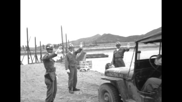 "stockvideo's en b-roll-footage met two us soldiers in jeep driving towards bridge on imjin river, south korean soldier standing guard in foreground / another jeep with words ""us war... - mp"