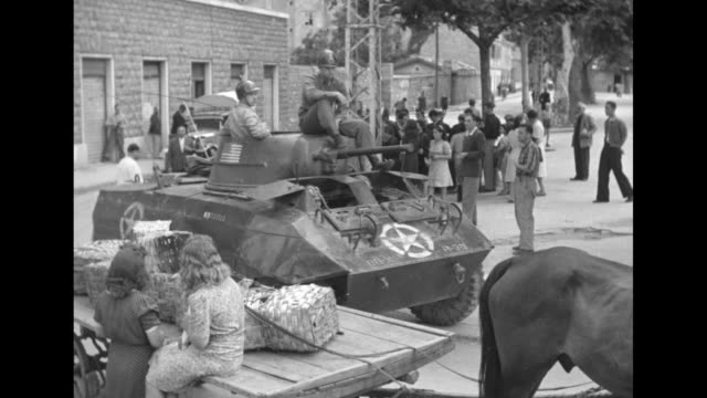 two us soldiers sitting on top of armored vehicle parked in square / vehicle drives away / same vehicle drives down street and turns corner and... - 1946 stock-videos und b-roll-filmmaterial