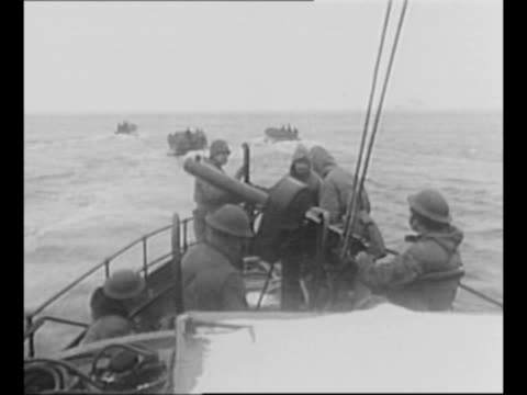 two us soldiers stand in gun turret of transport ship as us flag flies from mast behind / rear shot troops in prow of ship with gun as landing barges... - invasion beach stock videos & royalty-free footage