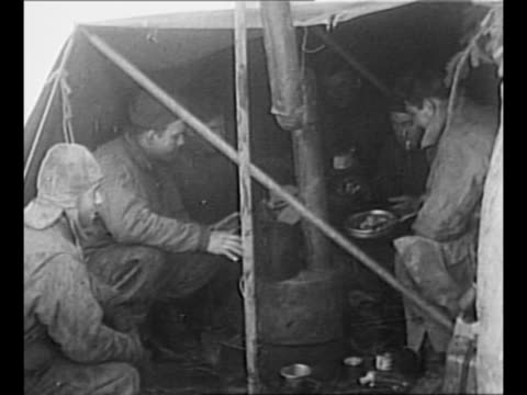 Two US soldiers stand outside small snowcovered tent in Belgium during World War II / group of bundledup soldiers huddles around small stove inside...