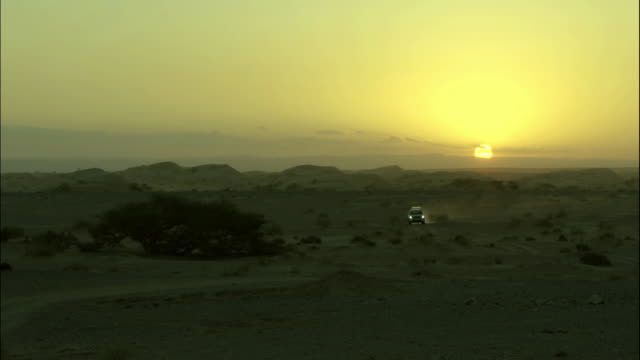 two vehicles in wadi araba desert at sunset, jordan - sports utility vehicle stock-videos und b-roll-filmmaterial