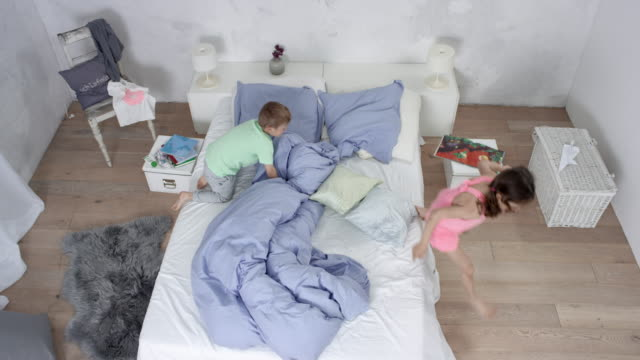 two very cute little kids (brother and sister) having great fun in bedroom