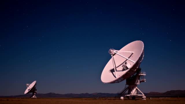 two very large array radio telescopes swivel around in synchronization. - 天体望遠鏡点の映像素材/bロール