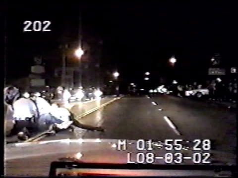 vídeos de stock e filmes b-roll de / two video angles of story nighttime dashcam footage officer arrives on scene where very large black man possibly intoxicated in middle of road /... - rodear
