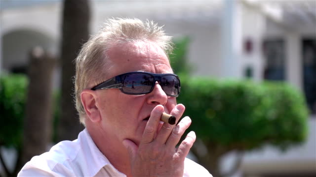two videos of businessman smoking cigar in real slow motion - millionnaire stock videos & royalty-free footage