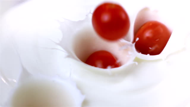 two videos of cherry tomatoes falling into yogurt-real slow motion - cherry tomato stock videos & royalty-free footage