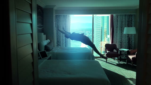 vídeos de stock e filmes b-roll de two videos of man jumping on the bed in real slow motion - hotel