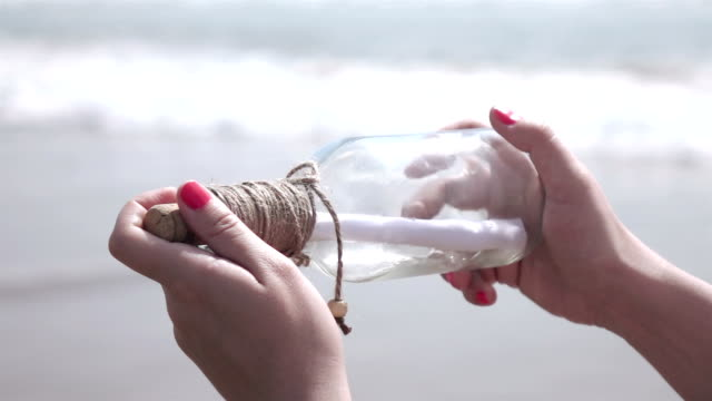 two videos of message in the bottle on the beach-slow motion - cork stopper stock videos & royalty-free footage