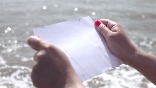 vídeos de stock e filmes b-roll de dois vídeos de papel na mão pelo oceano-câmara lenta - encontrar