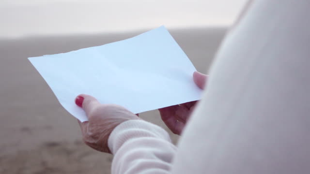 Two videos of paper in hands by the ocean-slow motion