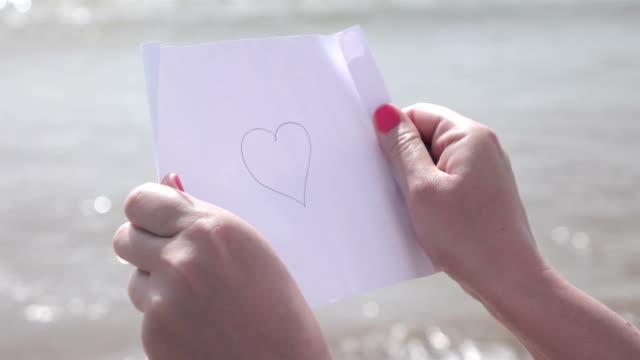 Due video di carta con messaggio per le mani al rallentatore