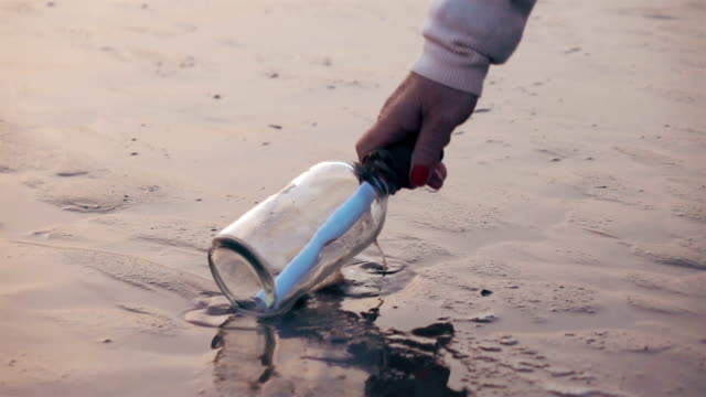 two videos of picking up message in a bottle-slow motion - cork stopper stock videos & royalty-free footage