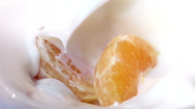 Two videos of pieces of orange falling into yogurt-real slow motion