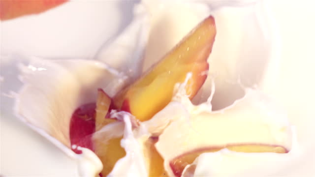 Two videos of pieces of peach falling into yogurt-real slow motion