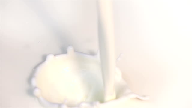 two videos of pouring fresh milk in real slow motion - smoothie stock videos & royalty-free footage