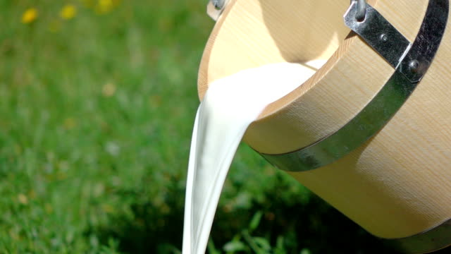 two videos of pouring milk from wooden bucket-real slow motion - pouring stock videos & royalty-free footage