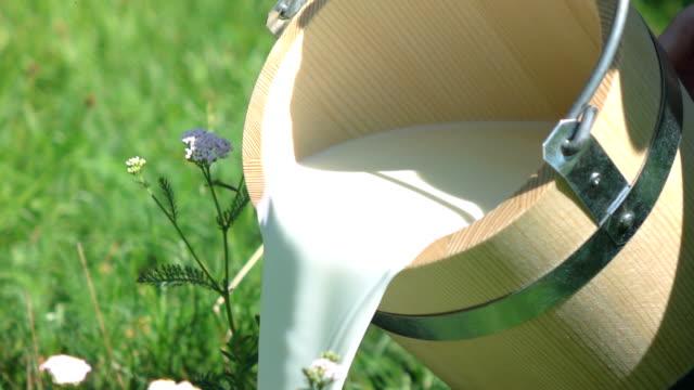 Zwei videos von Eimer gießen Milch aus Holz-real Zeitlupe
