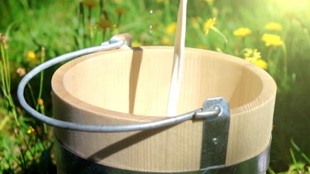 Zwei videos von gießen Milch in Holz Korb-real Zeitlupe