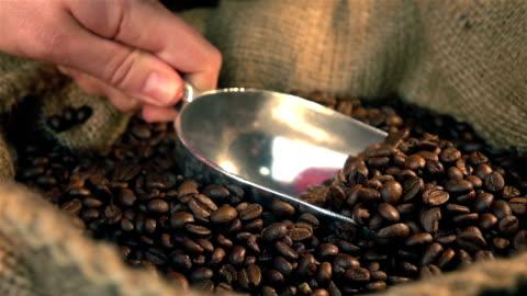 vídeos y material grabado en eventos de stock de dos vídeos de inserción ofrecen anticuchareo granos de café en reales en cámara lenta - bean
