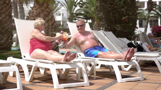 Twee video's van senior paar drinken van cocktails-real slow motion