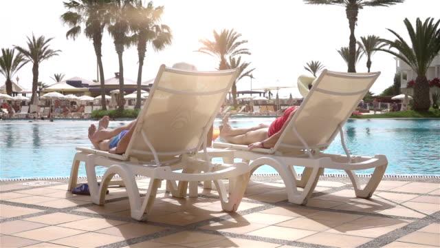 vídeos de stock e filmes b-roll de dois vídeos de casal sénior relaxante no real solários em câmara lenta - apanhar sol