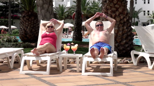 two videos of senior couple sitting on the sunbeds-slow motion - sunbathing stock videos & royalty-free footage