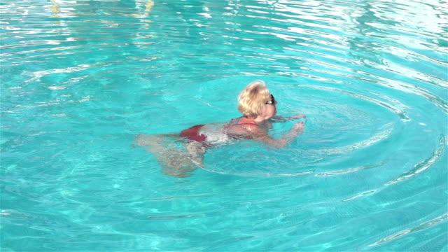 Zwei videos von Ältere Frau Schwimmen im Swimmingpool im real Zeitlupe